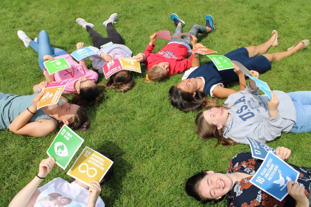 children lying in a circle looking at books